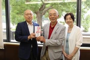 同窓会費の一部を竹内会長(左)に手渡す冨田さん(中央)と田中さん=柏原高校で